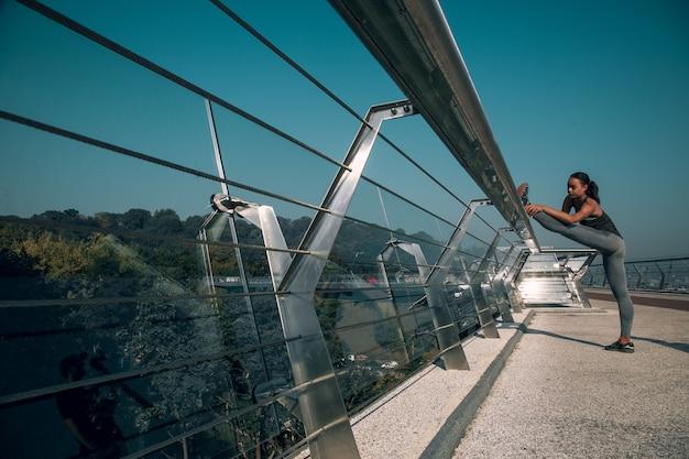 Sportive debout sur le pont avec son pied sur la rampe et étirant sa jambe. bannière de site web
