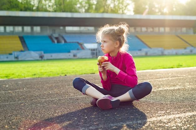 Sportive enfant fille mange des pommes