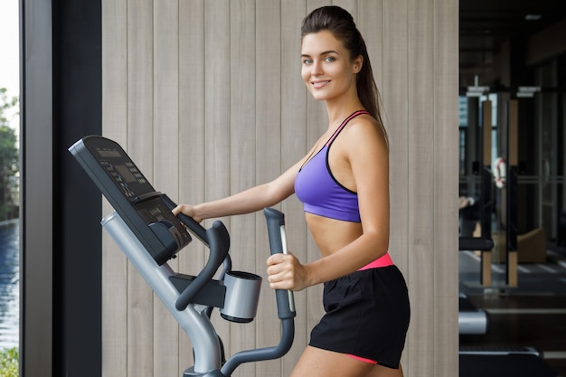 Sportive est une femme utilisant un vélo elliptique