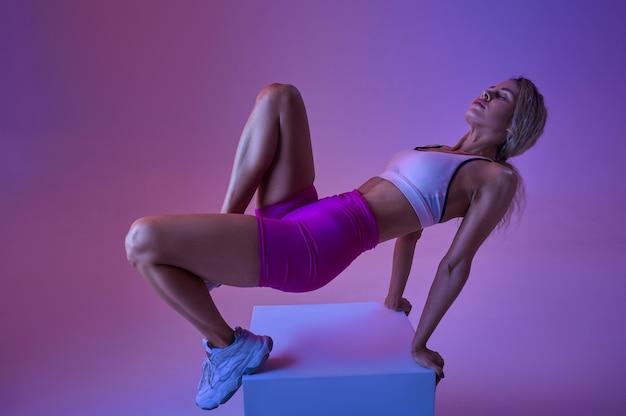 Sportive faisant de l'exercice en studio, fond néon