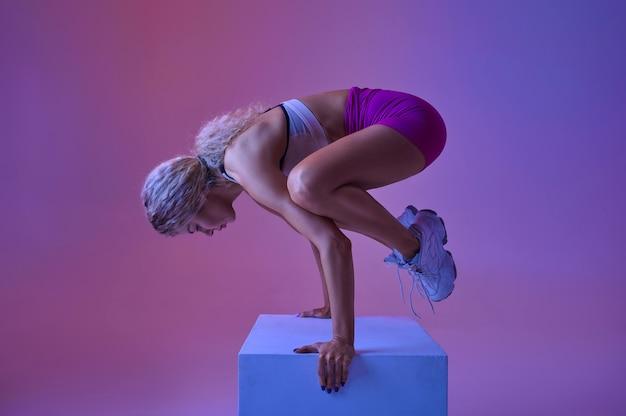 Sportive faisant des exercices d'équilibre en studio, fond néon. femme de remise en forme à la séance photo, concept sportif, motivation de style de vie actif