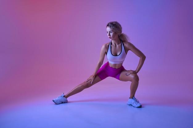 Sportive faisant des exercices d'étirement en studio, fond néon. femme de remise en forme à la séance photo, concept sportif, motivation de style de vie actif