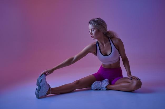 Sportive faisant des exercices d'étirement en studio, fond néon