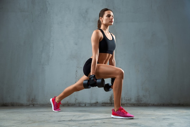 Sportive faisant des mouvements brusques à l'aide d'haltères