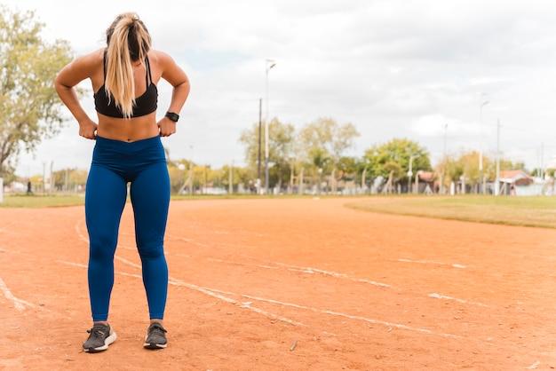Sportive femme debout sur la piste du stade