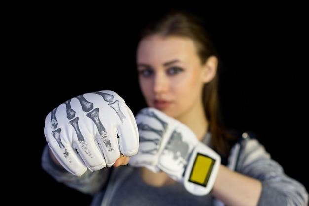 Sportive fille en gants de boxe sur fond noir.