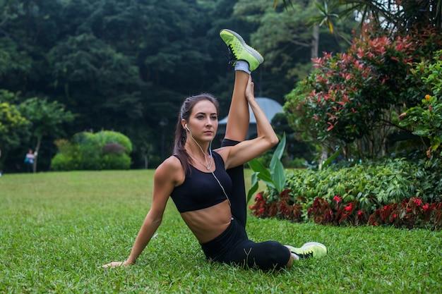 Sportive flexible jeune femme faisant des ischio-jambiers étirement des exercices sur l'herbe à l'extérieur. active fit girl training in park