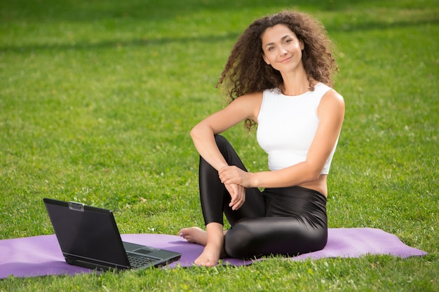 Sportive jeune femme assise sur l'herbe avec ordinateur portable