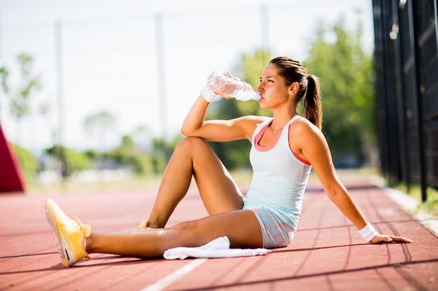 Sportive jeune femme buvant de l'eau