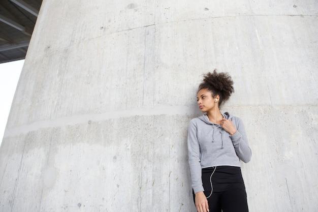 Sportive jeune femme debout à l'extérieur avec des écouteurs