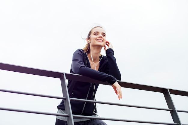 Sportive, jeune femme, à, écouteurs, s'appuyer, clôture, et, regarder loin, dehors