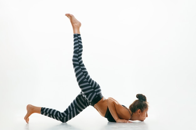 Sportive jeune femme faisant la pratique du yoga isolé sur blanc