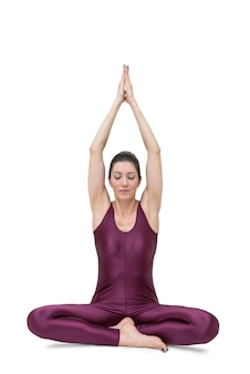 Sportive jeune femme faisant de la pratique du yoga isolé sur fond blanc