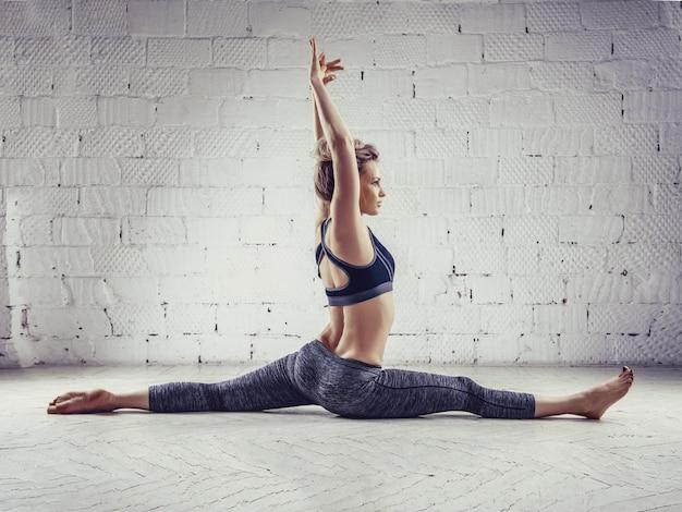 Sportive jeune femme faisant la pratique du yoga isolée sur fond blanc