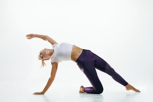 Sportive jeune femme faisant la pratique du yoga isolée sur un mur blanc. fit modèle féminin flexible pratiquant. concept de mode de vie sain et équilibre naturel entre le corps et le développement mental.