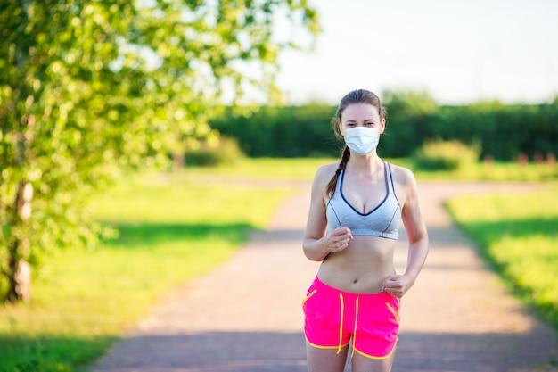 Sportive jeune femme fit dans le parc. fille de coureur caucasien sain vivant un mode de vie sain.
