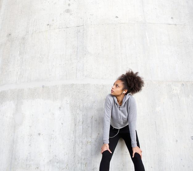 Sportive jeune femme se détendre à l'extérieur avec des écouteurs
