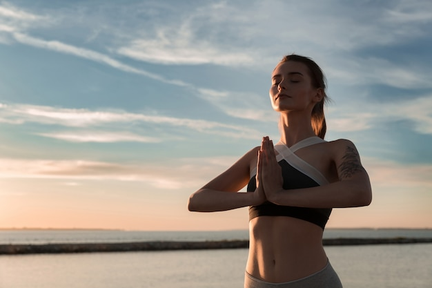 La sportive à la plage fait des exercices de méditation.