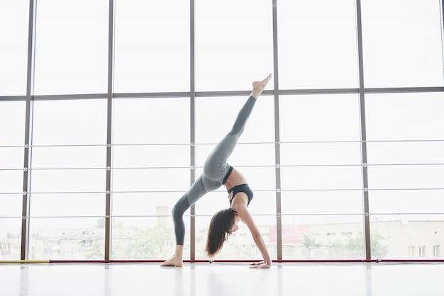 Une sportive qui fait des cours de yoga, étire ses jambes près de la grande fenêtre