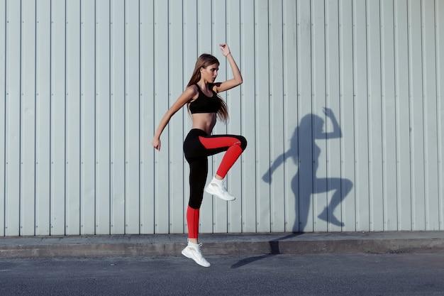Sportive sautant et s'étirant. toute la longueur d'une femme en bonne santé faisant de l'exercice et sautant à l'extérieur.