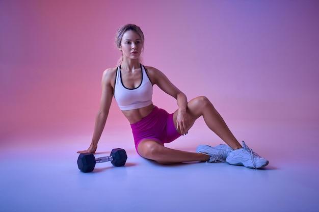 Sportive sexy pose avec haltère en studio, fond néon. femme de remise en forme à la séance photo, concept sportif, motivation de style de vie actif