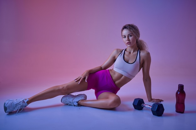 Sportive sexy pose avec haltère en studio, fond néon