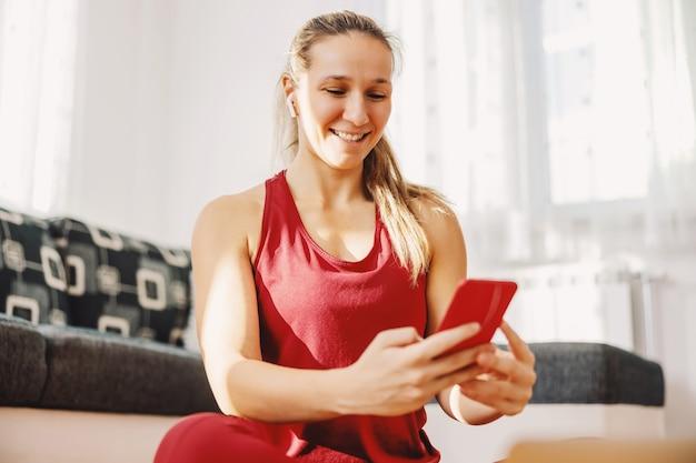 Sportive souriante assise sur le sol à la maison et accrochée aux médias sociaux.