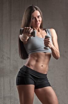Sportive souriante faisant coup de poing avec haltère dans un intérieur brutal