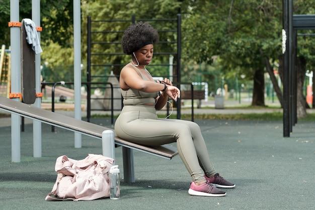 Sportive de taille plus en survêtement regardant une montre-bracelet