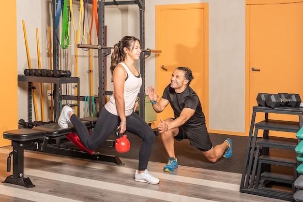 Sportive en tenue de sport faisant des fentes avec un kettlebell à la main avec une jambe posée sur un banc avec l'aide d'un entraîneur en salle de sport. concept d'exercice avec équipement en salle de sport.