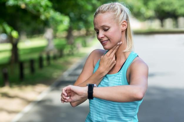 Sportive vérifiant sa montre de fréquence cardiaque