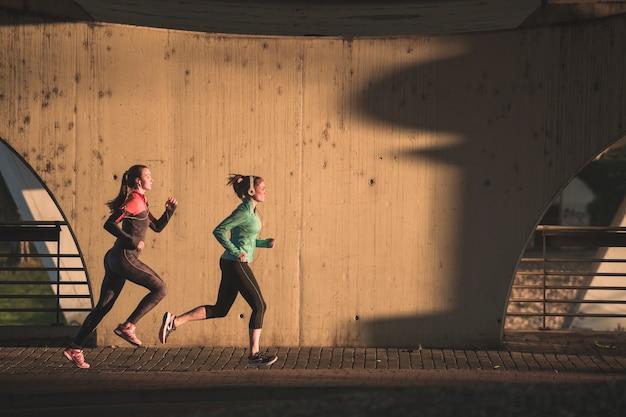 Sportives en cours d'exécution au coucher du soleil