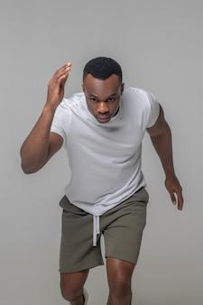 Sports, course à pied. sérieux jeunes adultes afro-américains concentrés dans des vêtements de sport légers fonctionnant énergique sur fond clair