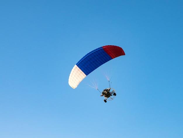 Sports extrêmes. parachute motorisé contre le ciel bleu.