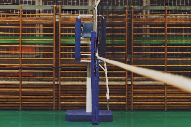 Sports image d'un filet de volley-ball dans une ancienne salle de sport vide avec tour d'arbitre. contexte pour le jeu de volley-ball en équipe. concept de sport, de mode de vie sain et de réussite en équipe. espace de copie