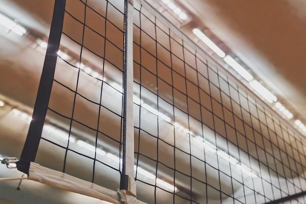 Sports image d'un filet de volley-ball dans une ancienne salle de sport vide vue d'en bas. contexte pour le jeu de volley-ball en équipe. concept de sport, de mode de vie sain et de réussite en équipe. espace de copie