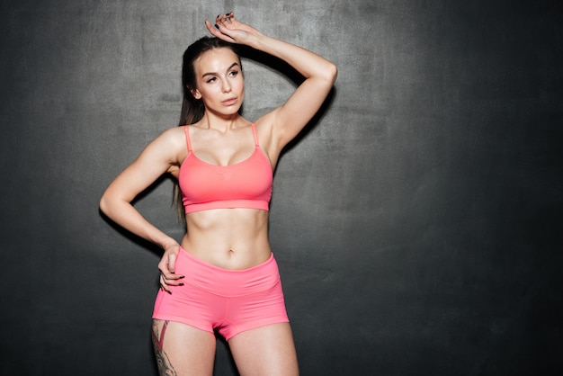 Sports jeune femme debout et posant sur le mur noir