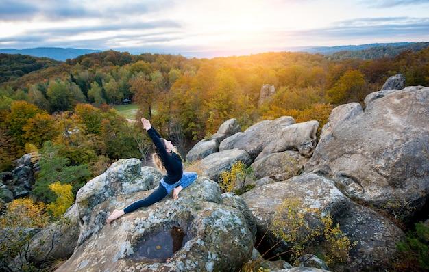 Sporty fit femme pratique le yoga au sommet de la montagne