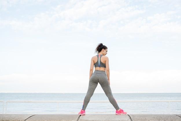 Sporty girl posant sur parapet par river