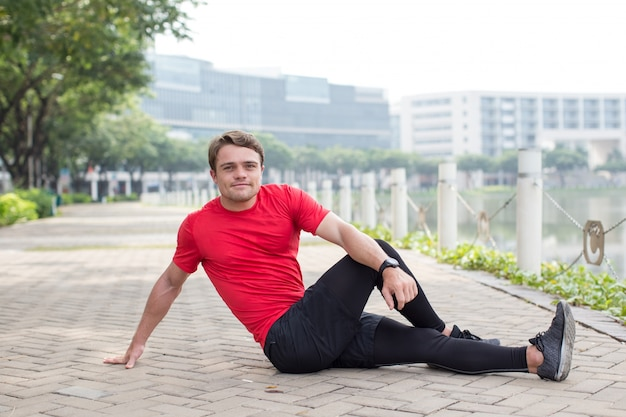 Sporty young man stretching body on pavement