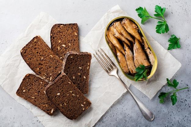 Sprats en conserve en boîte de conserve avec une fourchette avec du pain pour faire un sandwich sur le vieux béton gris. mise au point sélective