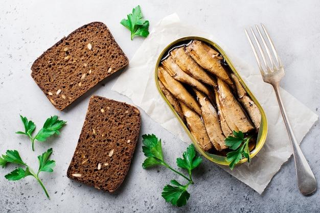 Sprats en conserve dans une boîte de conserve avec une fourchette avec du pain pour faire un sandwich sur béton vieux gris