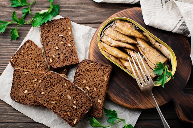 Sprats en conserve dans une boîte de conserve avec une fourchette avec du pain pour faire un sandwich sur une surface brun foncé