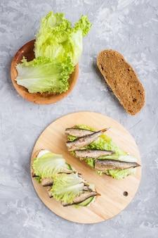 Sprats sandwichs avec laitue et fromage à la crème sur planche de bois sur un fond de béton gris