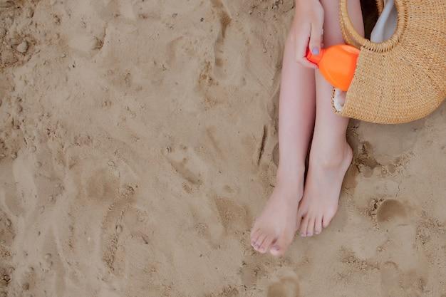 Spray d'huile de fille bronzant ses jambes protection contre les rayons uv du soleil mettant un écran solaire lotion crème solaire