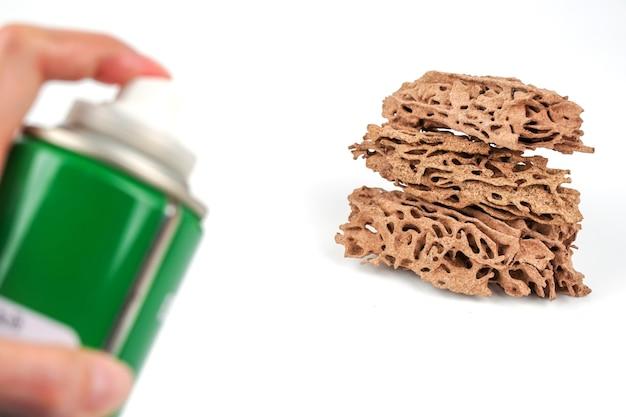 Spray insectifuge dans la main des hommes et des termitières isolés sur fond blanc