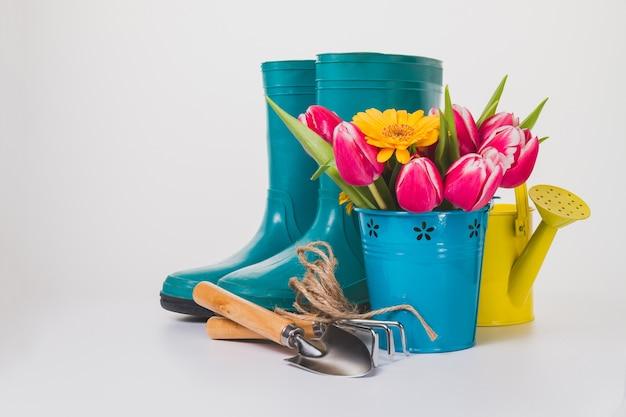 Spring background avec des fleurs décoratives et plusieurs outils de jardinage
