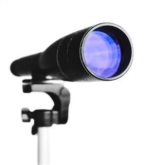 Spyglass ou télescope sur trépied isolé sur fond blanc. vue rapprochée sur l'objectif du télescope.