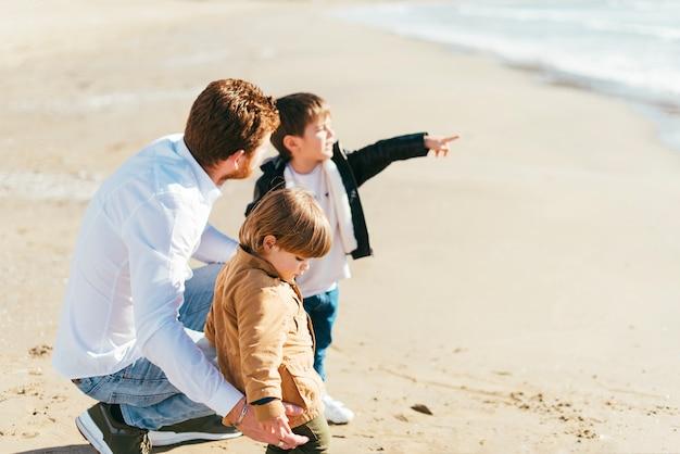 Squatting père avec fils sur la plage