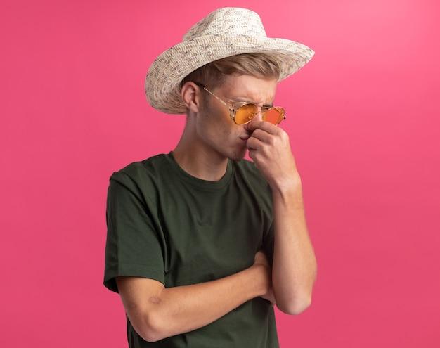 Squeamish jeune beau mec portant une chemise verte et des lunettes avec un chapeau saisi le nez isolé sur un mur rose